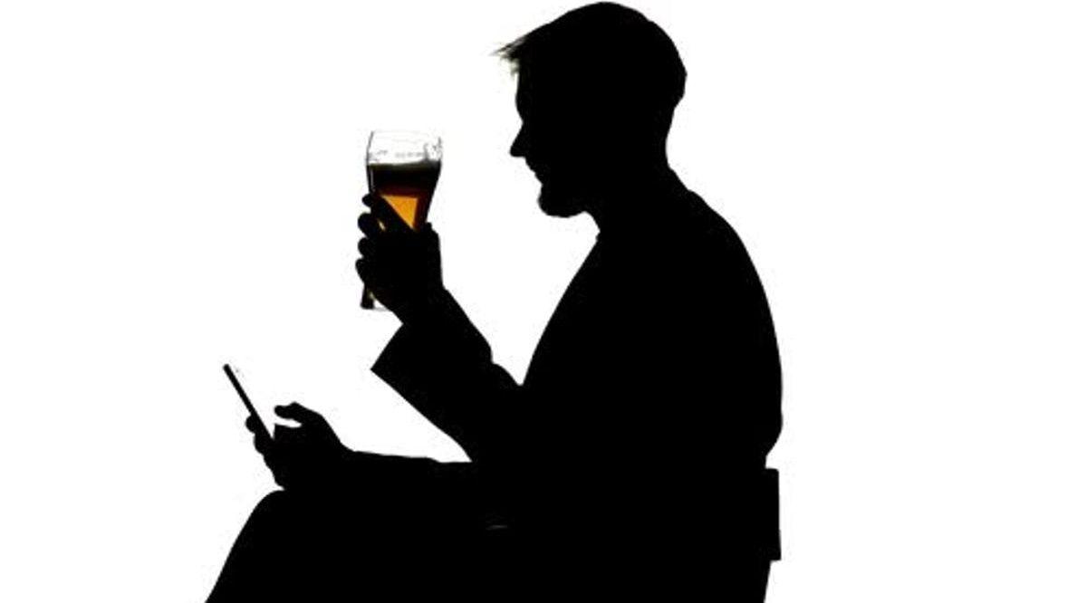 hombre bebiendo con movil